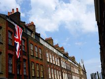 London: East End Georgian terrace houses. Georgian terrace houses (1726) in Spitalfields, London, with modern mosque at end of street stock image