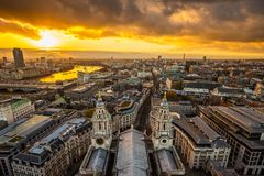 London, England - Aerial panoramic skyline view of London taken from top of St.Paul`s Cathedral at sunset. With beautiful golden sky and clouds royalty free stock photography