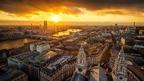 London, England - Aerial panoramic skyline view of London taken from top of St.Paul`s Cathedral at sunset. With River Thames, beautiful golden sky and clouds stock image