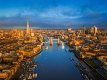 London, England - Aerial skyline view of London including iconic Tower Bridge with red double-decker bus. Tower of London, skyscrapers of Bank District and royalty free stock photography