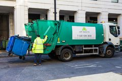 Garbage collector loads trash into his truck in London, England. LONDON, ENGLAND - 10 APRIL 2017 - Garbage collector loads trash into his truck in London stock images