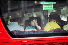 A boy of four looks at the rear window of a bus Stock Image
