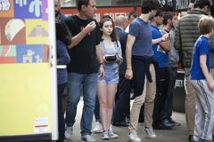 A girl in jeans shorts with a box of food scrambles through the crowd. LONDON, ENGLAND - AUGUST 22, 2017 A girl in jeans shorts with a box of food scrambles royalty free stock images