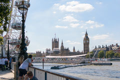 London, England - 30 August 2016: Unidentified people stand near London Eye admiring the view of river Thames. Unidentified people stand near London Eye admiring royalty free stock image