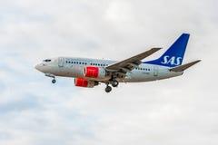 LONDON ENGLAND - AUGUSTI 22, 2016: Flygbolag Boeing 737 som för LN-RRD SAS landar i den Heathrow flygplatsen, London Arkivfoto