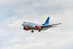 LONDON ENGLAND - AUGUSTI 22, 2016: Flygbolag Boeing 737 som för LN-RRD SAS landar i den Heathrow flygplatsen, London Arkivfoton