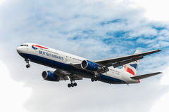 LONDON ENGLAND - AUGUSTI 22, 2016: G-BZHA British Airways Boeing 767 som landar i den Heathrow flygplatsen, London Arkivbild