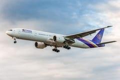 LONDON ENGLAND - AUGUSTI 22, 2016: HS-TKX Thai Airways Boeing 777 som landar i den Heathrow flygplatsen, London Arkivbild