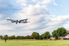 LONDON ENGLAND - AUGUSTI 22, 2016: HS-TKX Thai Airways Boeing 777 som landar i den Heathrow flygplatsen, London Arkivfoto