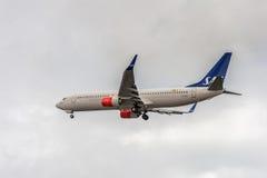 LONDON ENGLAND - AUGUSTI 22, 2016: LN-RGI Boeing 737 SAS skandinaviska flygbolag som landar i den Heathrow flygplatsen, London Royaltyfri Bild