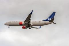 LONDON ENGLAND - AUGUSTI 22, 2016: LN-RGI Boeing 737 SAS skandinaviska flygbolag som landar i den Heathrow flygplatsen, London Arkivbild
