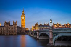 London, England - The beautiful Big Ben and Houses of Parliament at sunrise with clear blue sky. And red double decker bus royalty free stock photos