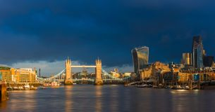 London, England - Beautiful golden sunrise in London with Tower Bridge, St.Paul`s Cathedral and skyscrapers. Of Bank District. Dramatic dark clouds at Stock Photo