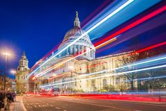 London, England - Beautiful Saint Paul`s Cathedral with iconic red double decker buses on the move. With light trails at night Royalty Free Stock Images