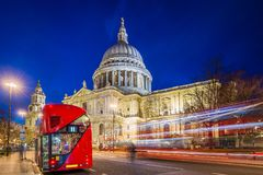 London, England - Beautiful Saint Paul`s Cathedral with traditional red double decker bus at night. With busses and cars passing by Stock Image