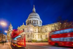 London, England - Beautiful Saint Pauls Cathedral with iconic red double decker buses. On the move at night Royalty Free Stock Photography