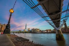 London, England - Beautiful sunset scene at Millennium Bridge with famous skyscraper Stock Photography