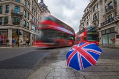 London, England - British umbrella at busy Regent Street with iconic red double-decker buses. On the move Royalty Free Stock Photos
