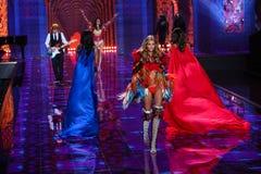LONDON, ENGLAND - DECEMBER 02: Ed Sheeran performs as model Kate Grigorieva walks the runway Stock Image