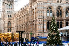 People in the Christmas skating rink by the Natural History Museum. The famous museum is one of t. LONDON, ENGLAND - December 2016: People in the Christmas royalty free stock photo