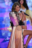 LONDON, ENGLAND - DECEMBER 02:  Singer Taylor Swift (L) perfoms on stage as model Blanca Padilla (R) model walks the runway Stock Photos