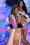 LONDON, ENGLAND - DECEMBER 02:Singer Taylor Swift (L) perfoms on stage as model Blanca Padilla (R) walks the runway Stock Image