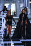 LONDON, ENGLAND - DECEMBER 02:  Taylor Swift (L) performs as model Karlie Kloss walks the runway Stock Photography
