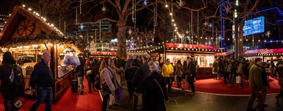 LONDON, ENGLAND, DECEMBER 10th, 2018: People having fun in a nicely illuminated christmas fair while walking around, shopping and stock image