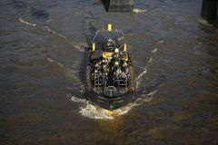 Tourists in lifejackets sail across the Thames on an inflatable rubber boat. LONDON, ENGLAND - December 18 , 2017 Tourists in lifejackets sail across the Thames royalty free stock image