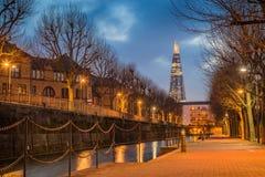 London, England - dekorativer Kanal an der blauen Stunde mit schönem Scherbewolkenkratzer stockbild