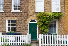 London, England, Europe - characteristic British brick wall house facade. With green door and white fence Stock Photos