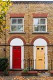 London, England, Europe - typical British style doors, windows and house facade. London, England, Europe - typical British style yellow and red doors, windows Royalty Free Stock Images
