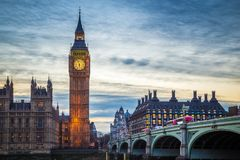 London, England - The famous Big Ben and Houses of Parliament with iconic red double decker buses. On Westminster Bridge at dusk Royalty Free Stock Images