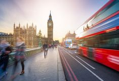 London, England - The iconic Big Ben and the Houses of Parliament with famous red double-decker bus. And tourists on the move on Westminster bridge at sunset Royalty Free Stock Images