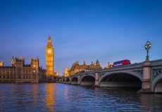 London, England - The iconic Big Ben with Houses of Parliament and traditional red double decker bus on Westminster Bridge. At sunrise with clear blue sky Royalty Free Stock Photo