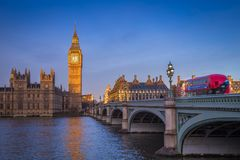 London, England - The iconic Big Ben with Houses of Parliament and traditional red double decker bus. On Westminster Bridge at sunrise with clear blue sky stock photography