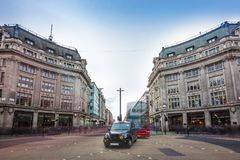 London, England - Iconic black taxi and red double decker bus at the famous Oxford Circus with Oxford Street and Regent Street. On a busy day royalty free stock image