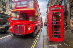 London, England - Iconic blurred black londoner taxi and vintage red double-decker bus on the move Royalty Free Stock Photo