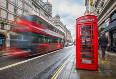 London, England - Iconic blurred red double-decker bus on the move with traditional red telephone box. In the center of London at daytime Royalty Free Stock Images