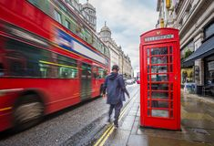London, England - Iconic blurred red double-decker bus on the move with traditional red telephone box and walking man. In the center of London at daytime Stock Images