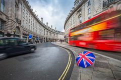 London, England - Iconic red double-decker bus and black taxi on the move on Regent Street. With british umbrella royalty free stock photography