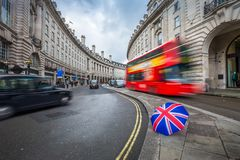 London, England - Iconic red double-decker bus and black taxies on the move on Regent Street. With british umbrella Royalty Free Stock Photos