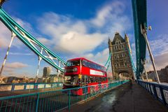 London, England - Iconic red double-decker bus in motion on famous Tower Bridge. With skyscraper of Bank District at background. Blue sky and clouds stock photos