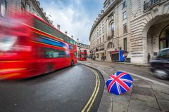 London, England - Iconic red double-decker buses and black taxi on the move on Regent Street. With british-style umbrella royalty free stock image