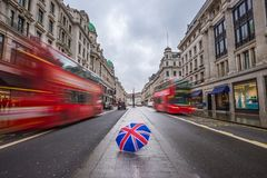 London, England - Iconic red double-decker buses on the move at busy Regent Street. With British umbrella Royalty Free Stock Photography