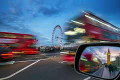 London, England - iconic red double-decker buses on the move on Westminster Bridge with Big Ben and Houses of Parliament. At background at blue hour royalty free stock photography