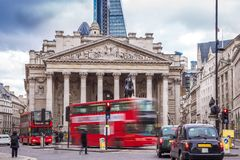 London, England - Iconic red double decker busses on the move and black and green london taxies with the Royal Exchange building. On a busy day Stock Photos