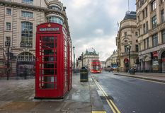 London, England - 15.03.2018: Iconic red telehone box near Piccadilly Circus with red double-decker bus. On the move Royalty Free Stock Images