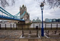 London, England - Iconic Tower Bridge with bench and street light on a cloudy day. With offices at background Stock Images