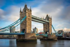 London, England - Iconic Tower Bridge with traditional red double-decker bus and skyscrapers of Bank District